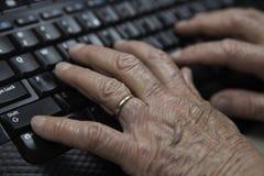 Gamla händer som skriver på tangentbordslut upp Arkivbild