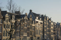 Gamla historiska byggnader i rad i Amsterdam i aftonen Royaltyfri Fotografi