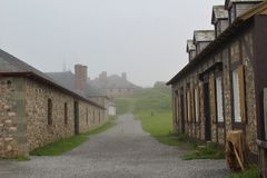 Gamla hus i byn i den historiska fästningen av Louisbourg, Breton ö för udde, på en dimmig dag arkivbild