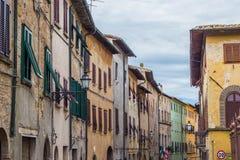 Gamla hus med rullgardiner i mitten av Volterra Arkivbild
