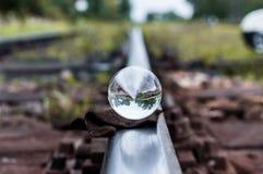 Gamla järnvägsspår med den glass sfären på dem och selektiv fokus arkivfoton