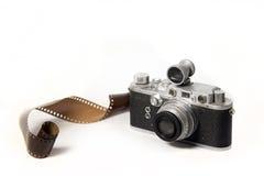 Gamla kamera och filmer på vit bakgrund Arkivfoton