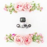 Gamla kamera och rosor, knoppar och sidor på vit bakgrund Lekmanna- lägenhet, bästa sikt retro bakgrund Arkivfoton