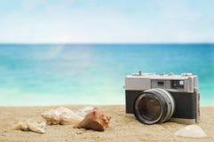Gamla kamera och skal på den sandiga stranden Royaltyfri Fotografi