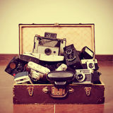 Gamla kameror i en gammal resväska Arkivfoto