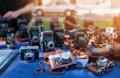 Gamla kameror säljs på en gatamarknad på en solig dag Arkivfoto