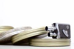 Gamla kanistrar för filmkamera och filmpå vit arkivfoton