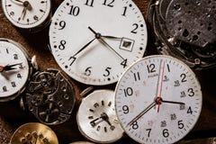 Gamla klockaframsidor som gör en bakgrund arkivfoto