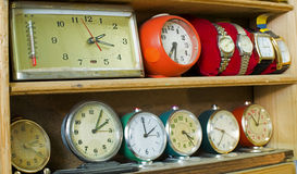 Gamla klockor på en hylla Arkivfoton