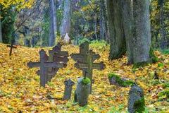 Gamla kors på gravar med höstsidor Royaltyfri Bild