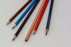 Gamla kulöra blyertspennor för närbild på vit bakgrund royaltyfria bilder