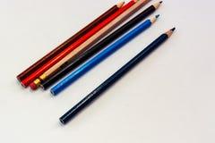 Gamla kulöra blyertspennor på den vita bakgrundsnärbilden arkivfoton