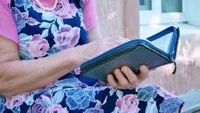 Gamla kvinnliga händer som rymmer den öppna boken stock video