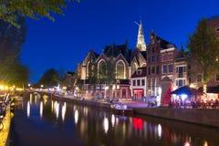 Gamla kyrkliga Oude Kerk och Amsterdam kanaler på natten, Nederländerna royaltyfri bild