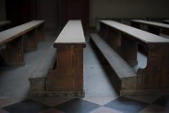 Gamla kyrkliga träbänkar med fattigt ljus i tom kyrka i Zagreb Royaltyfri Fotografi