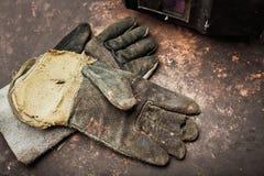 Gamla läderhandskar för welders på den rostiga tabellen Arkivfoto