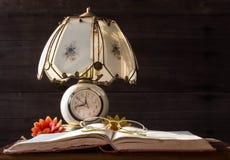 Gamla lampa och böcker med läs- exponeringsglas Arkivbild