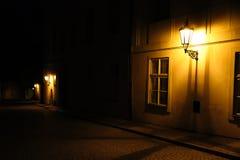 Gamla lyktor som exponerar en medeltida gata för mörk bakgata på natten i Prague, Tjeckien Lågt nyckel- foto med bruntgulingsigna arkivfoto
