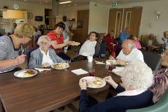 Gamla människor i ett vårdhem som har matställen Royaltyfria Bilder