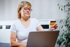 Gamla människor och modernt teknologibegrepp Stående av för mogen en hållande kreditkort kvinnahand för 50-tal, genom att använda Royaltyfri Foto