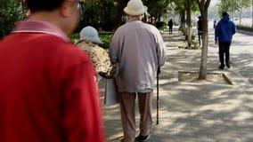 Gamla människor som långsamt går i gatan