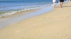 Gamla människor som tar en gå på stranden royaltyfria foton
