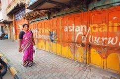 Gamla målade färgrika väggar av gatan och kvinnan som förbi går Fotografering för Bildbyråer