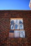 Gamla målade Windows i en tegelstenbyggnad under blå himmel Royaltyfri Fotografi