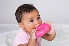 7 gamla månad behandla som ett barn att tugga på leksaken Arkivfoton