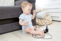 10 gamla månader behandla som ett barn dra kablar från elektrisk förlängning Royaltyfri Foto