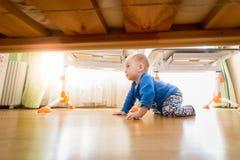 9 gamla månader behandla som ett barn krypning på trägolv på sovrummet Royaltyfri Foto