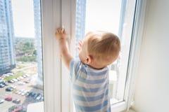 9 gamla månader behandla som ett barn pojkeanseende på fönsterbräda och att försöka att öppna fönstret Bbay i fara royaltyfri foto