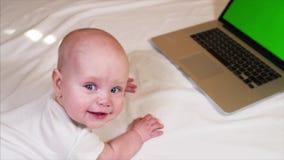 6 gamla månader behandla som ett barn pojken ligger på säng framme av bärbara datorn med chromatangentskärmen lager videofilmer