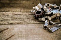 Gamla maskindelar i maskineri shoppar på träbakgrund gammal maskin med tappningbildstil Arkivfoton