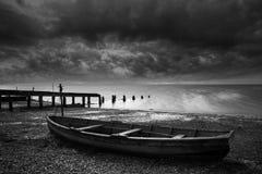 Gamla murkna ekor på kust av sjön med stormig himmeloverhe Royaltyfri Foto