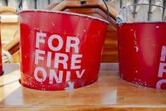 Gamla och slitna hinkar för röd brand i träställning royaltyfria bilder