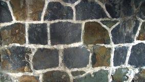 Gamla ojämna stenar väggen med vita skarvar arkivfoton