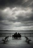 Gamla par sitter på en bänk Royaltyfri Foto