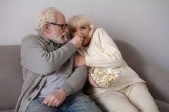 Gamla par som äter popcorn på soffan arkivfoto