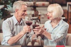 Gamla par som firar en årsdag tillsammans i ett kafé arkivbild