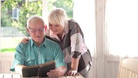 Gamla par som läser en bok