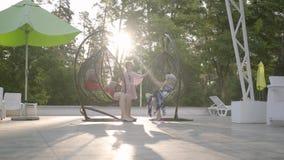 Gamla par som sitter på en hängande stol på solnedgången som tillsammans kopplar av i hotellkomplexet Gullig liten flicka som kör stock video