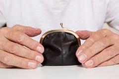 Gamla pensionärhänder och liten pengarpåse royaltyfria bilder