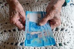 Gamla räknande pengar för äldre caucasian eyears för kvinna 90 i hennes händer arkivfoton