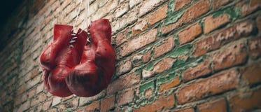 Gamla röda boxas handskar hänger på för att spika på tegelstenväggen med kopieringsutrymme för text Kickupplösning 3D framför royaltyfria foton