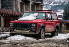 Gamla röda SUV med ett plant gummihjul Lantlig transport i de Carpathian bergen En vinterresa till och med Eastern Europe Royaltyfri Bild