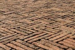 Gamla röda tegelstenar som stenlägger sicksackmodellen Arkivbild