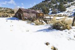 Gamla red ut spökstadbyggnader i öknen under vinter med snö Royaltyfri Foto