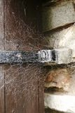 Gamla rengöringsdukar, spindel förtjänar i en gammal dörr vid en vägg royaltyfri foto