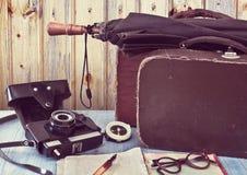 Gamla resväskor och en kamera. Ställ in handelsresanden. Royaltyfria Foton
